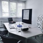 Ein Raum für Besprechungen und Meetings ausgestattet mit einem Beamer, Flipchart, Whiteboard, Moderationskoffer, einem Tisch und Stühle.